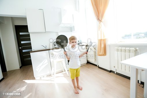 488109116 istock photo funny European little boy chef dancing,Happy weekend, boy wants to make pancakes, but the frying pan are too gay, he decided to have fun holding wooden spoons in his hands, having fun while cooking 1130691368