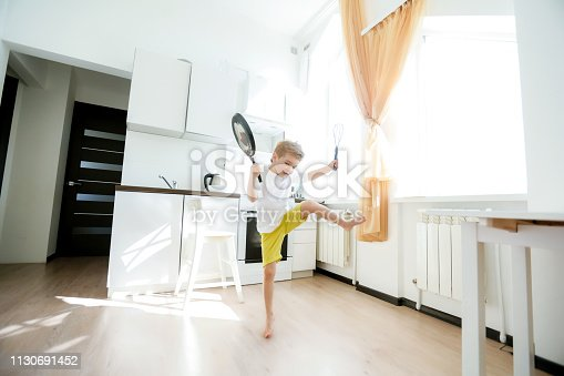 488109116 istock photo funny European little boy chef dancing,Happy weekend, boy wants to make pancakes, but the frying pan are too gay, he decided to have fun holding wooden spoons in his hands, having fun while cooking 1130691452