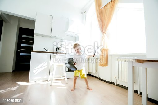 488109116 istock photo funny European little boy chef dancing,Happy weekend, boy wants to make pancakes, but the frying pan are too gay, he decided to have fun holding wooden spoons in his hands, having fun while cooking 1130691532