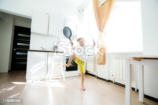 488109116 istock photo funny European little boy chef dancing,Happy weekend, boy wants to make pancakes, but the frying pan are too gay, he decided to have fun holding wooden spoons in his hands, having fun while cooking 1130691561