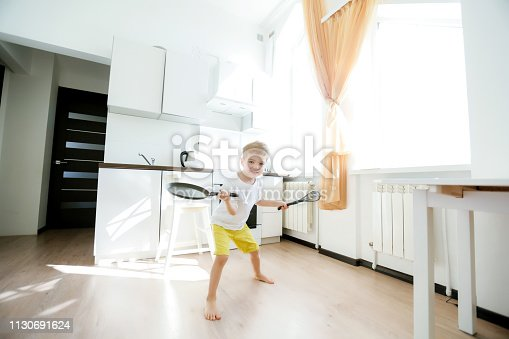 488109116 istock photo funny European little boy chef dancing,Happy weekend, boy wants to make pancakes, but the frying pan are too gay, he decided to have fun holding wooden spoons in his hands, having fun while cooking 1130691624