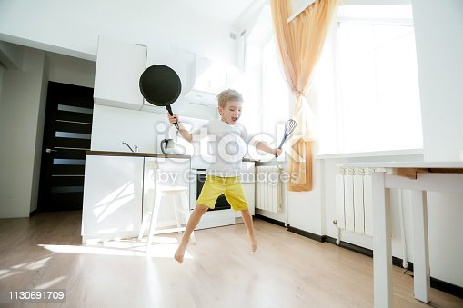 488109116istockphoto funny European little boy chef dancing,Happy weekend, boy wants to make pancakes, but the frying pan are too gay, he decided to have fun holding wooden spoons in his hands, having fun while cooking 1130691709