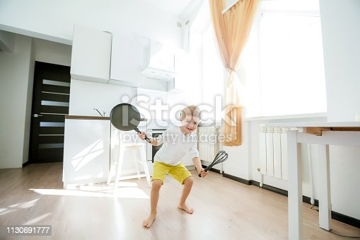 488109116istockphoto funny European little boy chef dancing,Happy weekend, boy wants to make pancakes, but the frying pan are too gay, he decided to have fun holding wooden spoons in his hands, having fun while cooking 1130691777