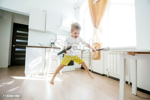 488109116 istock photo funny European little boy chef dancing,Happy weekend, boy wants to make pancakes, but the frying pan are too gay, he decided to have fun holding wooden spoons in his hands, having fun while cooking 1130691887