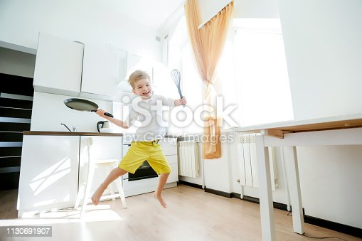 488109116 istock photo funny European little boy chef dancing,Happy weekend, boy wants to make pancakes, but the frying pan are too gay, he decided to have fun holding wooden spoons in his hands, having fun while cooking 1130691907