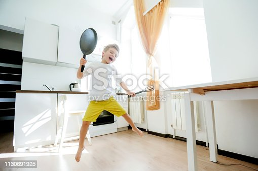 488109116 istock photo funny European little boy chef dancing,Happy weekend, boy wants to make pancakes, but the frying pan are too gay, he decided to have fun holding wooden spoons in his hands, having fun while cooking 1130691925