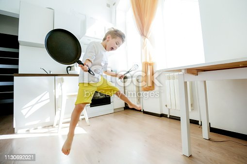 488109116 istock photo funny European little boy chef dancing,Happy weekend, boy wants to make pancakes, but the frying pan are too gay, he decided to have fun holding wooden spoons in his hands, having fun while cooking 1130692021
