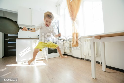 488109116istockphoto funny European little boy chef dancing,Happy weekend, boy wants to make pancakes, but the frying pan are too gay, he decided to have fun holding wooden spoons in his hands, having fun while cooking 1130692072