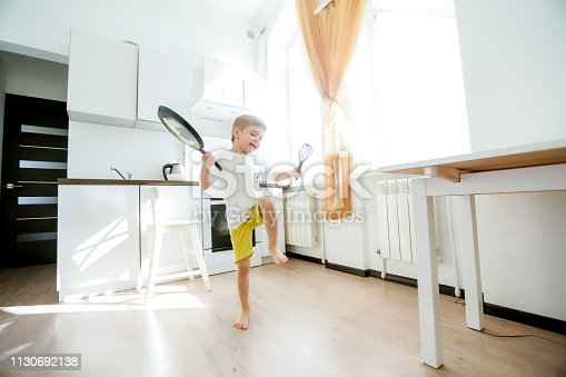 488109116istockphoto funny European little boy chef dancing,Happy weekend, boy wants to make pancakes, but the frying pan are too gay, he decided to have fun holding wooden spoons in his hands, having fun while cooking 1130692138