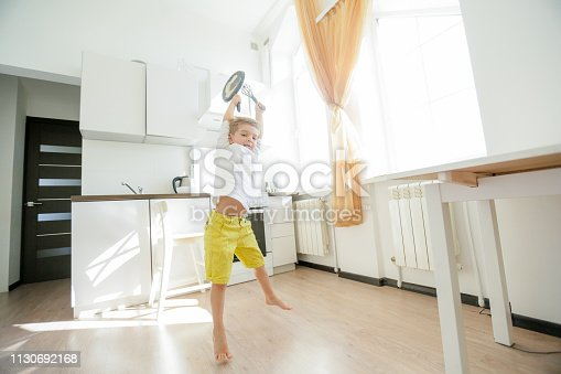 488109116 istock photo funny European little boy chef dancing,Happy weekend, boy wants to make pancakes, but the frying pan are too gay, he decided to have fun holding wooden spoons in his hands, having fun while cooking 1130692168