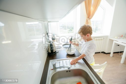 488109116 istock photo funny European little boy chef dancing,Happy weekend, boy wants to make pancakes, but the frying pan are too gay, he decided to have fun holding wooden spoons in his hands, having fun while cooking 1130692378