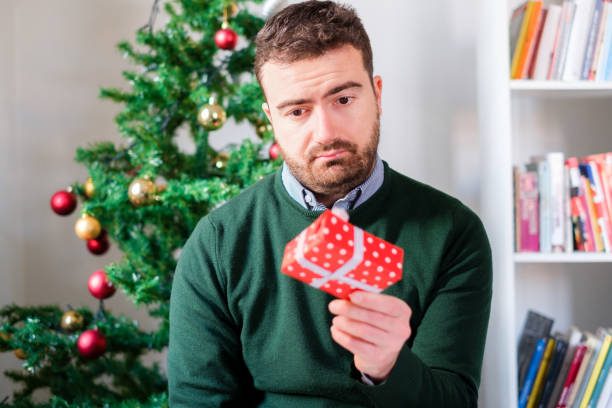 funny face of a man disappointed by the small gift box - disappointment stock pictures, royalty-free photos & images