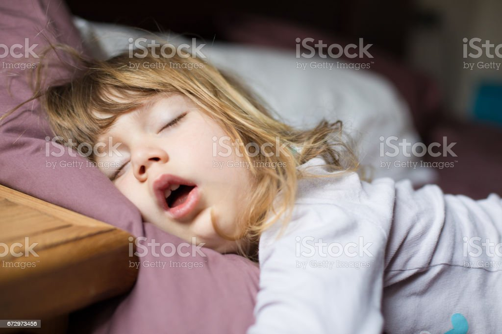 funny face of child sleeping on king bed stock photo