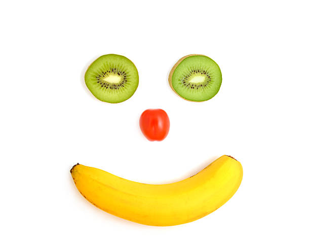 Funny face out of banana, tomato and kiwi on white stock photo