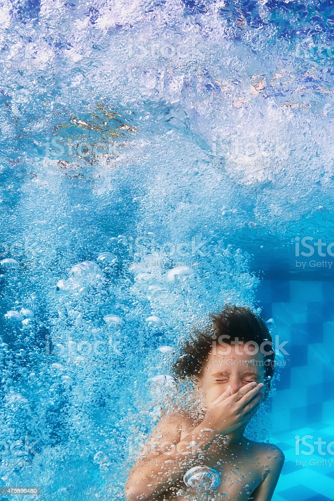 Funny face portrait of smiling child swimming underwater in pool stock photo