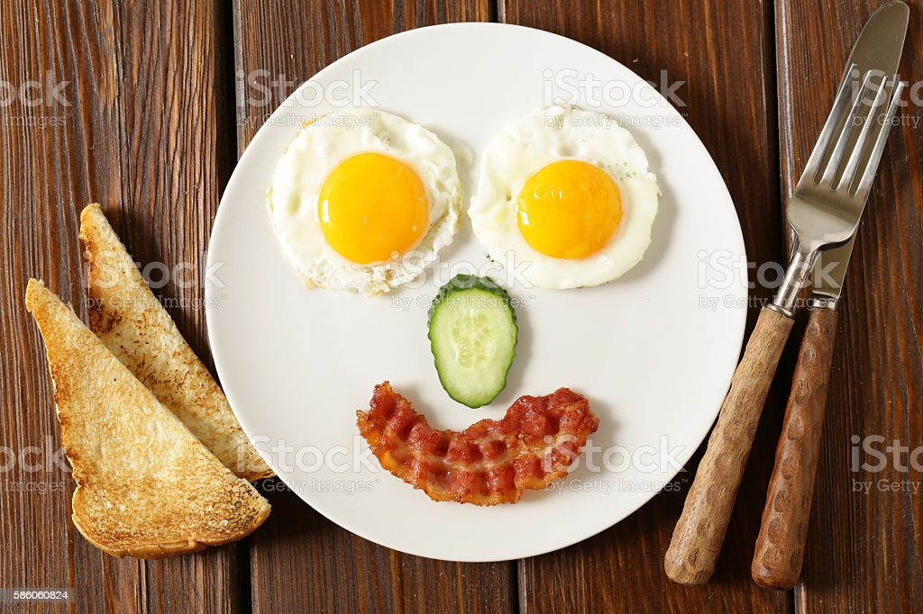 funny face serving breakfast, fried egg and toast stock photo