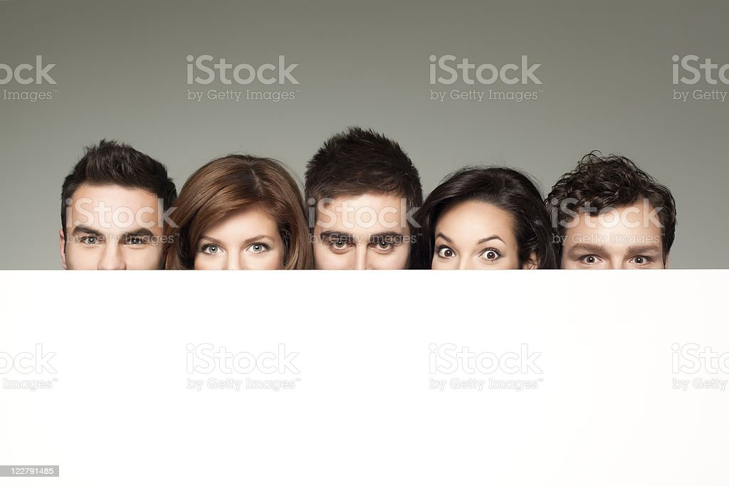 funny faces behind white board royalty-free stock photo