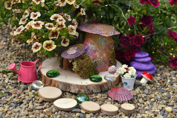 Funny fairy dollhouse on wooden planks by flowerbed with petunia flowers in the garden. stock photo