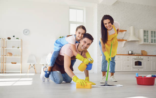 Funny family cleans the room in the house. stock photo