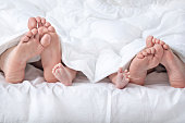 Funny family feet under the blanket