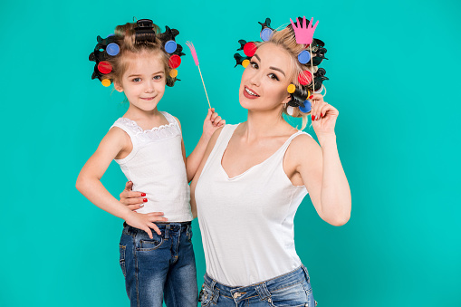 Funny family Mother and her child daughter girl with a paper accessories