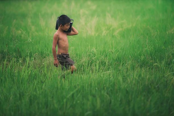 funny farmer boy playing in green rice field. - radio kultur stock-fotos und bilder