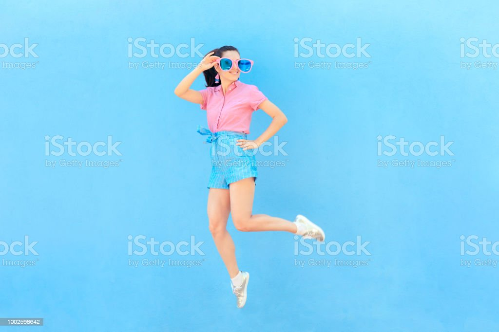 Funny Fashion Girl with Oversized Sunglasses and Jumping stock photo