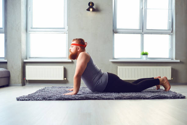 A Funny Fat Bearded Man In Sports Clothes Does Yoga The Room Stock Photo