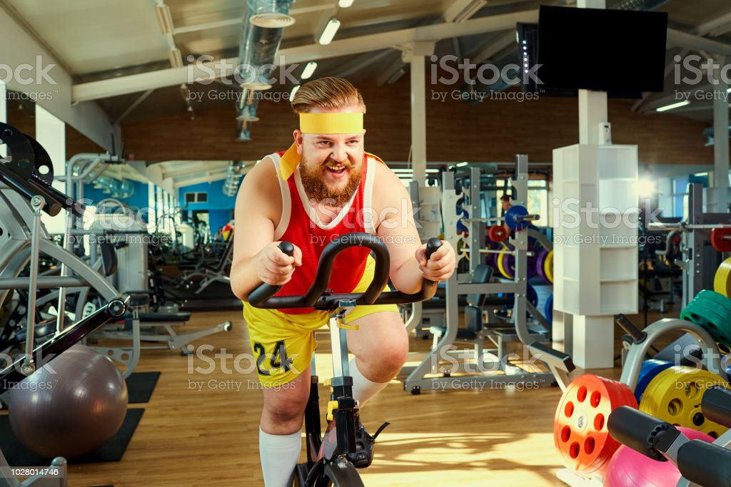 A funny fat man with a beard doing exercises on an exercise bike in a...
