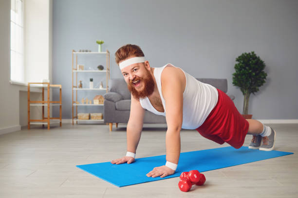 Funny fat man doing exercises on the floor smiling on the floor at home. stock photo