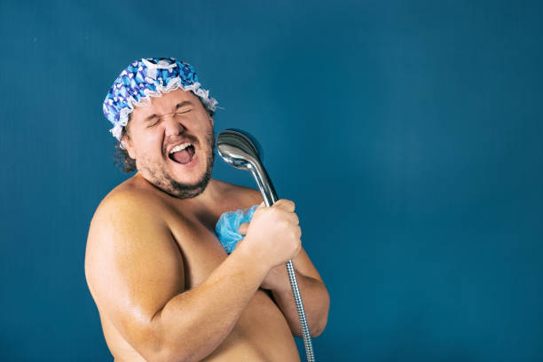 Funny fat man in blue cap sing in the shower Funny fat man in blue cap sing in the shower. Fun and cleanliness singing stock pictures, royalty-free photos & images