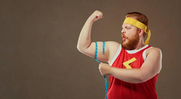 un hombre gordo divertido en ropa deportiva mide el brazo con un centim - hombres grandes musculosos fotografías e imágenes de stock