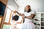 Funny father with tutu skirts dancing like ballerinas