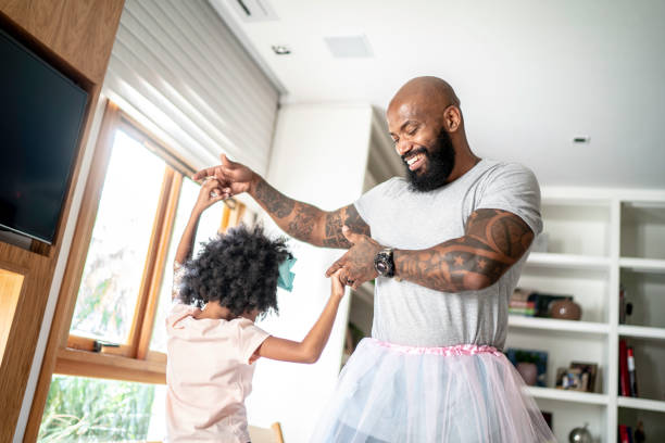 Funny father with tutu skirts dancing like ballerinas stock photo