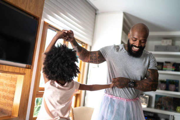 Funny father with tutu skirts dancing like ballerinas Funny father with tutu skirts dancing like ballerinas stay at home father stock pictures, royalty-free photos & images