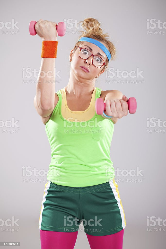 Funny female wearing glasses doing exercises with small pink weights royalty-free stock photo