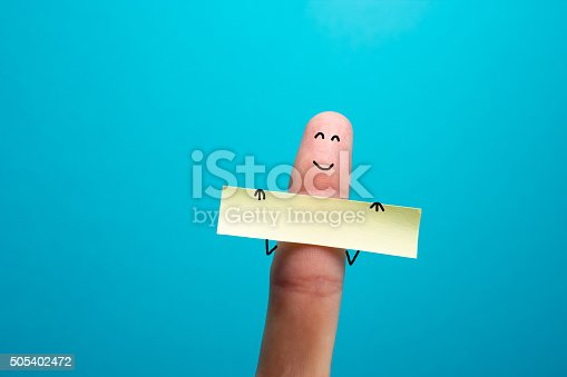 istock Funny finger holding blank bunner showing on it and smiling 505402472