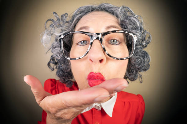 Funny Fisheye Nerdy Older Woman Blowing Kisses A humorous fisheye image of an older, nerdy woman blowing kisses. sdominick stock pictures, royalty-free photos & images