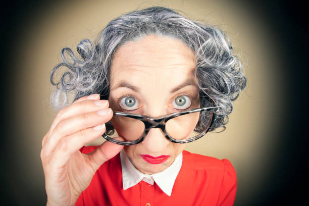 Funny Fisheye Nerdy Older Woman Looking Over Glasses A humorous fisheye image of an older, nerdy woman looking over her large glasses. sdominick stock pictures, royalty-free photos & images