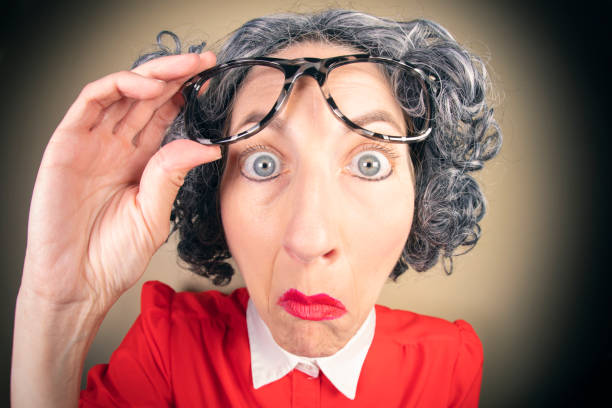 Funny Fisheye Nerdy Older Woman Looking Without Glasses A humorous fisheye image of an older, nerdy woman looking under her large glasses. sdominick stock pictures, royalty-free photos & images