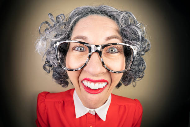 Funny Fisheye Nerdy Older Woman A humorous fisheye image of an older, nerdy woman with a big geeky smile. sdominick stock pictures, royalty-free photos & images