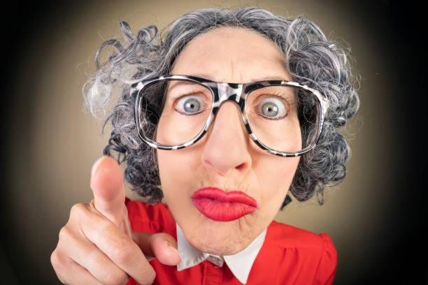 Funny Fisheye Nerdy Older Woman Pointing Finger Being Stern A humorous fisheye image of an older, nerdy woman looking stern and pointing her finger. sdominick stock pictures, royalty-free photos & images