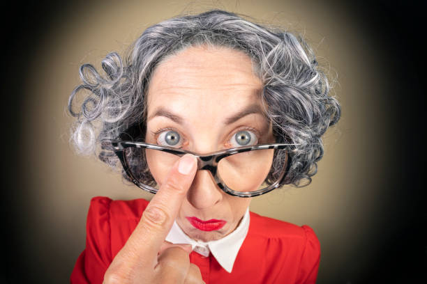 Funny Fisheye Nerdy Older Woman Pushing Up Glasses A humorous fisheye image of an older, nerdy woman pushing up her glasses. sdominick stock pictures, royalty-free photos & images