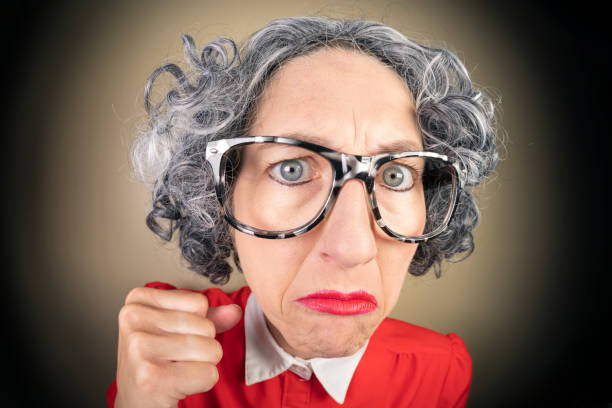 Funny Fisheye Nerdy Older Woman Ready to Fight A humorous fisheye image of an older, nerdy woman looking stern and holding up a fist. sdominick stock pictures, royalty-free photos & images