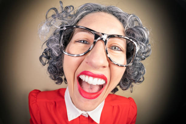 Funny Fisheye Nerdy Older Woman With Big Smile A humorous fisheye image of an older, nerdy woman with a big dorky smile. sdominick stock pictures, royalty-free photos & images