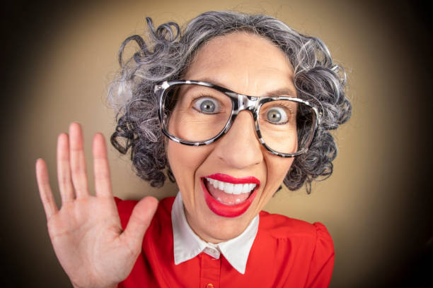 Funny Fisheye Older Nerdy Woman Waving A funny fisheye image of an older nerdy woman smiling and waving. sdominick stock pictures, royalty-free photos & images