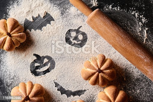 istock Funny food for halloween. Homemade sweet cakes in shape of pumpkin on a dark background 1163857590
