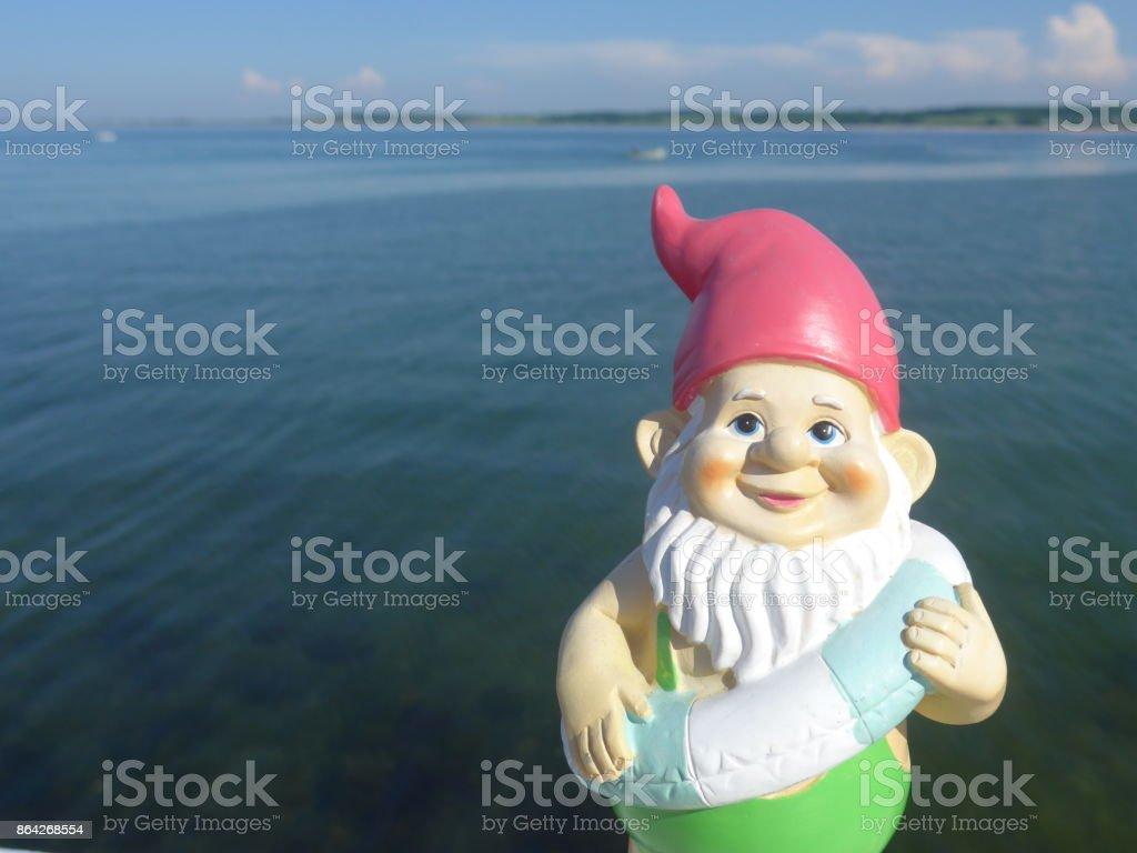 Funny garden dwarf makes seaside holiday royalty-free stock photo