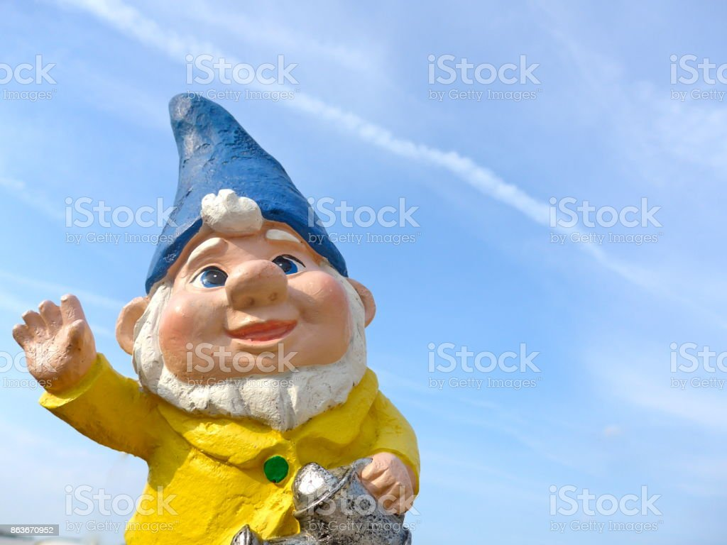 Funny garden dwarf with blue hat makes seaside holidays stock photo