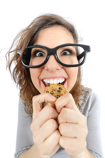 Funny geek girl eating a cookie Funny geek girl eating a cookie isolated on a white background nerd hairstyles for girls stock pictures, royalty-free photos & images